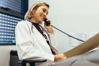 Female Doctor Reading Medical Reports And Talking On Phone At Clinic